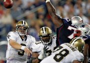 New Orleans quarterback Drew Brees (9) passes as Vince Wilfork, upper right, tries to block the ball. The Patriots held off the Saints, 27-24, on Thursday in Foxborough, Mass.