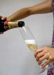 "Champagne is being poured in a ""beer-like way,"" achieved by tilting the glass and gently sliding the Champagne down its inside wall into the flute, Thursday in Paris to illustrate a theory by French scientists from University of Reims. French scientists there, in the home of Champagne, have determined that pouring bubbly on a slant like you would a beer is actually a better way to serve Champagne because it preserves more of the tiny gas bubbles that improve the drink's flavor and aromas. Glasses that are chilled more also retain more bubbles."