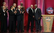 Members of the 1960 U.S. Olympic team applaud as Jerry West, second from right, and Oscar Robertson, right, shake hands during ceremonies at the Naismith Memorial Basketball Hall of Fame on Friday in Springfield, Mass. At far left is former Jayhawk guard Al Kelley.
