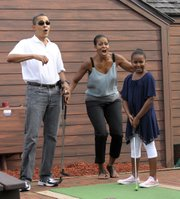 President Barack Obama and first lady Michelle Obama react as their daughter Sasha gets a hole-in-one on the first hole as they play miniature golf Saturday at Pirate's Island Golf in Panama City Beach, Fla. The Obamas are spending the weekend in Florida.