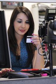New Mexico Motor Vehicle Division employee Catalina Chavez enters data from a customer's driver's license Aug. 5 at a motor vehicle field office in Albuquerque, N.M.
