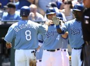 Kansas City's Willie Bloomquist (8) is congratulated by Wilson Betemit, right, and Alex Gordon after scoring the lone run on Billy Butler's single in the first inning of a 1-0 victory over the Yankees on Sunday in Kansas City, Mo.