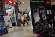 Customers enter a mobile phone shop as a billboard of a BlackBerry phone is placed at the entrance last week in Calcutta, India.