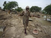 Pakistani flood survivors return to their village devastated by heavy floods Monday in Dera Ismail Khan, Pakistan. A forecast of more flooding has increased the urgency of the massive international relief effort.