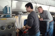 KU graduate student and research assistant Lei Shi, left, consults Electrical Engineering Professor Chris Allen, technical director of CReSIS, on radar settings during an October 2009 research flight.