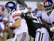 New York Giants quarterback Eli Manning escapes a tackle attempt by the New York Jets' Shaun Ellis, center, as the Giants' Kareem McKenzie, right, tries to help Manning. Manning left the game with a gash to his head that required 12 stitches Monday at the New Meadowlands Stadium in East Rutherford, N.J.