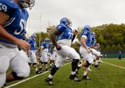 Kansas offensive lineman Jeremiah Hatch, 77, warms up with his teammates during practice Tuesday, Aug. 17, 2010.