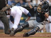 Cleveland Indians catcher Chris Gimenez, right, keeps the ball in his glove after tagging Kansas City Royals' Mitch Maier out at home as Maier tried to advance on a fly out by Chris Getz during the second inning. The Royals won, though, 9-7, on Wednesday in Kansas City, Mo.