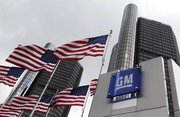 American flags fly outside General Motors world headquarters in Detroit in this April 21, 2009, file photo. General Motors filed the first batch of paperwork Wednesday needed to sell stock to the public, a step that brings the automaker closer to shedding government ownership.