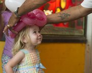 Delilah Pellow, 3, Lawrence, is crowned with a balloon princess hat during Busker Fest in downtown Lawrence. Although Friday night's activities were cut short due to severe weather, the festival runs through the rest of the weekend.
