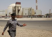 An Iranian security guard directs media Saturday at the Bushehr nuclear power plant, with the reactor building seen in the background, just outside the southern city of Bushehr, Iran.