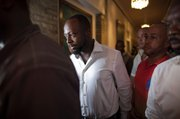 Haitian-born singer and presidential hopeful Wyclef Jean, second left, walks surrounded by security after Haiti's Electoral Council rejected his candidacy Friday in Port-au-Prince, Haiti.