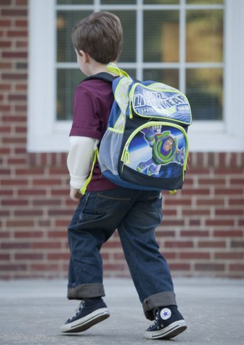A young boy wearing his Buzz Lightyear backpack races to class at New York School.
