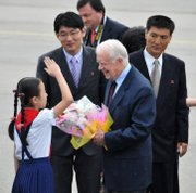 A child salutes former U.S. President Jimmy Carter, center, Wednesday upon his arrival at the airport in Pyongyang, North Korea, in this photo released by China's Xinhua News Agency.  Carter arrived in North Korea on Wednesday on a mission U.S. officials said was aimed at bringing home an imprisoned American.