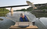Jason Goeckler of the Kansas Department of Wildlife and Parks ducks to avoid a silver carp that came shooting out of the Kansas River near Kansas City, Kan., in this July 2006 file photo. Two types of carp have become established in rivers across Kansas.