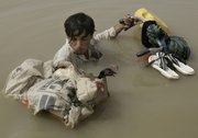 A Pakistani man negotiates floodwaters with his chickens Saturday at the remote villages of Ali Pur town in Muzaffargarh district, Punjab Province, Pakistan. Floodwaters made another break Saturday in the levees protecting a southern Pakistani city, as thousands of residents fled for high ground and left the city nearly empty.