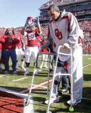Oklahoma receiver corey wilson takes a few steps out of his wheelchair at the end of OU's senior day ceremony last season.