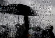 Visitors try to stay dry as rain falls on a monument that lists names of victims of Hurricane Katrina who lived in St. Bernard Parish before a memorial service to commemorate the fifth anniversary of the storm Sunday in Shell Beach, La.