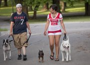 Amanda Brittain, left, and Renee Rivera walk their dogs, from left, Lyric, Lola and Snowflake. Snowflake was adopted recently from the Lawrence Humane Society and is fitting in well with the other family dogs.