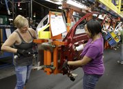 Patti Burkel, left, and Tasha Livingston install wiring in a car door at General Motors' Lordstown Assembly plant June 15 in Lordstown, Ohio.
