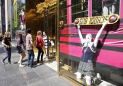 Teenagers enter a Juicy Couture store July 30 that features a window display with back-to-school clothing in New York. The nation's retailers are reporting surprisingly solid gains for August.