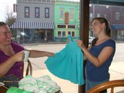 Erika Shearer, Lawrence, left, looks over a dress Carrie Wendel-Hummell made for her 4-year-old daughter at a recent Stitch 'n' Bitch meeting at Mirth Cafe, 745 N.H.