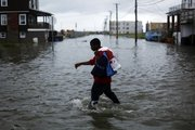 Ibn McKinney, 14, walks through a flooded street in Atlantic City, N.J., Friday as Hurricane Earl moves up the eastern coast. Earl weakened on its way to New England.