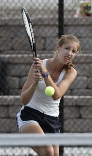 Lawrence High's Morgan Manger hits a backhand during a quad at the LHS courts on Wednesday.