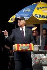 "Vice President Joe Biden hands out hot dogs to the troops during an appearance Wednesday on the ""Colbert Report"" in this photo provided by Comedy Central."