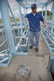 Bryan Baumann, Eudora, a water plant operator at Clinton Water Treatment Plant, collects water samples Thursday from settling tanks before running a series of tests on the water.