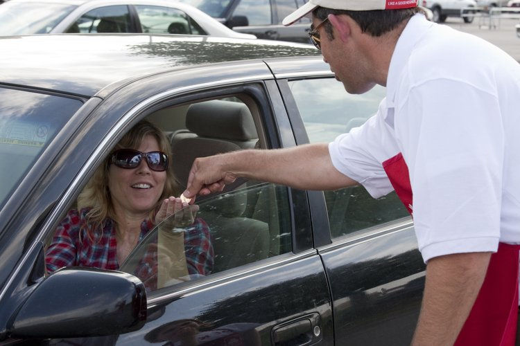Drivers were treated to a surprise Sept. 10, 2010, while cruising through the parking lot at Dillons, Sixth Street and Wakarusa Drive, with their seat belts on. Mary Shipley, Eudora, smiles as State Farm agent Kurt Goeser hands her a $1 coin. The seat belt campaign — a partnership between State Farm, Safe Kids Kansas and the Kansas Department of Transportation — is taking place again in Lawrence and 55 other cities through Kansas. The only change is that volunteers will be handing out $1 bills instead of coins.