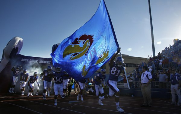 Johnathan Wilson leads the charge onto the field carrying a Jayhawk flag.