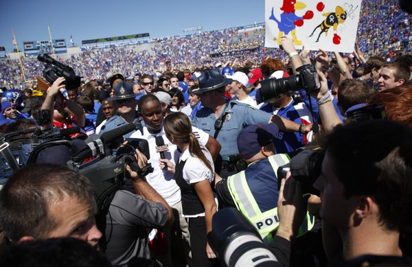Media and fans swarm coach Turner Gill after the Jayhawks upset Georgia Tech.
