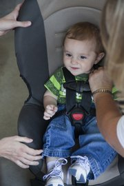 Eight-month-old Christian Boyette, Ozawkie, seems happy getting fitted in his new car seat with the helping hands from his mother and a volunteer with Safe Kids.