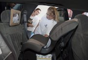 Dena Bracciano, a volunteer with Safe Kids of Douglas County Coalition, checks out a new car seat for Melissa Boyette, left, of Ozawkie, in September 2010.