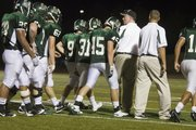 Free State head coach Bob Lisher meets his defense as they walk off the field after surrendering a touchdown to Shawnee Mission West during their matchup Friday night. A blocked extra point would prove costly for the Firebirds, as they lost their first game of the season, 21-20.