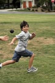 Jimmy Alexander, 7, a second-grader at Hillcrest School, attempts to avoid a ball thrown at him during a game of town ball at Water Tower Park. The games are family-friendly, with cursing and strict competition frowned upon.