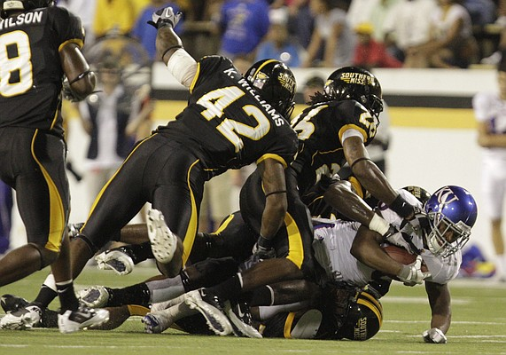 Kansas running back Deshaun Sands falls under a pile of Southern Miss defenders during the first quarter, Friday, Sept. 17, 2010 at M.M. Roberts Stadium in Hattiesburg, Mississippi.