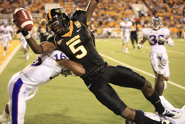 Southern Miss receiver DeAndre Brown extends toward the goal line as he is hit by Kansas cornerback Chris Harris during the third quarter, Friday, Sept. 17, 2010 at M.M. Roberts Stadium in Hattiesburg, Mississippi.