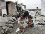 Girls play beside an open sewer Sept. 2 in the sprawling slum on the edge of the Philippines' Manila Bay. The U.N. is holding a summit starting Monday to review progress being made to tackle poverty, disease, ignorance and inequality.