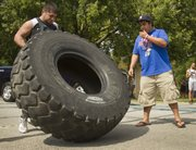Benjamin Fuentes, left, of Santana, Kan., flips a 400-pound tractor tire with encouragement from his friend Daniel Garcia Saturday at the second annual Lawrence Next Level Games strongman competition at Watson Park.