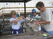 Judi Salyer, right, helps Aiden Sothers, left, and Kevin Monge, center, capture and identify bugs they caught as part of the Auburn-Washburn USD 437 Squirmy Science program. The environmental outdoor classes are held on 66 acres of land north of Washburn Rural Middle School.