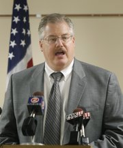Calumet County District Attorney Ken Kratz reads from a prepared statement announcing that he will step down from his position during a news conference at the Calumet County Courthouse on Friday in Chilton, Wis.