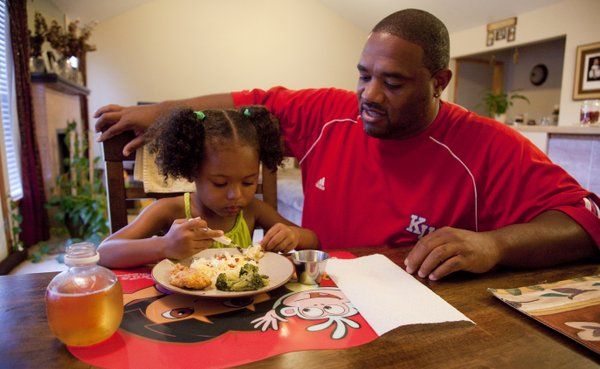 Vince Downing helps his 3-year-old daughter Mackenzi with her meal on Wednesday, Sept. 22, 2010, as his wife, Dawn, finishes up in the kitchen. The Downings have family dinners about five times a week.
