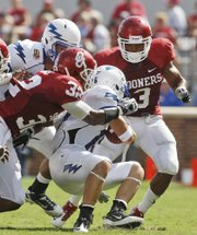 Oklahoma defensive back Jonathan Nelson, right, moves in to aid cornerback Jamell Fleming, left, with a tackle of Air Force wide receiver Jonathan Warzeka, center, in the Sooners' victory Saturday in Norman, Okla. Oklahoma will play its first road game on Saturday in Cincinnati.
