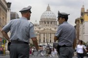 Italian financial police officers talk to each other in front of St. Peter's square Tuesday at the Vatican. Just when the Catholic Church didn't need another scandal, Italian authorities have seized $30 million from a Vatican bank account and begun investigating top officials of the Vatican bank in connection with a money laundering probe.