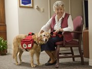 Carol Floersch sits with Rally, a service dog who has been visiting Presbyterian Manor with chaplain Dottie Scholtz. Rally was trained specifically for ministerial purposes and working with the elderly.