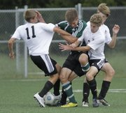 Free State soccer players from left, Zackary Thompson (11) Tony Libeer (7) and Ruben Ghijsen (5) collide around a Shawnee Mission South player in the Firebirds game against Shawnee Mission South at FSHS Thursday.