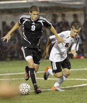 Lawrence High soccer player Nick Haig (8) right, attempts to run down an opponent with the ball in the Lions game against Olathe Northwest at LHS Thursday.
