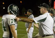 Free State head coach Bob Lisher talks one-on-one with Firebird lineman Caylor Norris after a play during Free State's game against Shawnee Mission North Friday night.